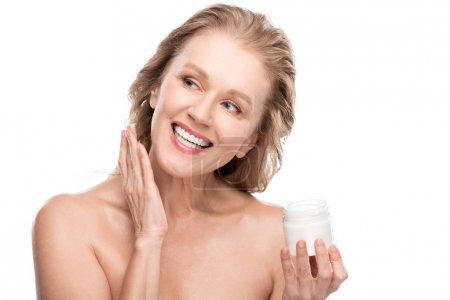 Photo pour Belle femme mûre avec la peau parfaite appliquant la crème cosmétique et souriant isolated on White - image libre de droit