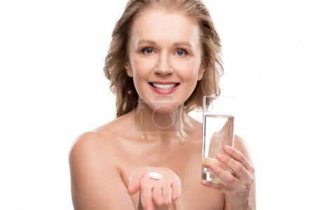 nude mature woman with glass of water and pills Isolated On White