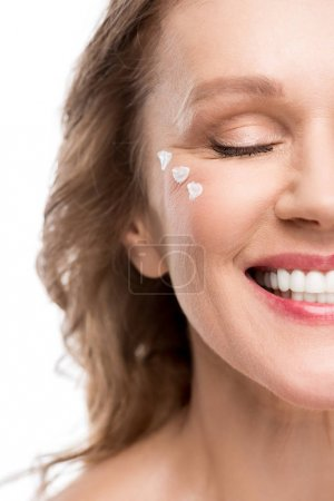 Photo for Smiling mature woman with cosmetic cream on face Isolated On White - Royalty Free Image