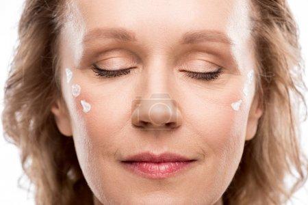 Photo pour Femme mature avec crème cosmétique sur le visage et les yeux fermés isolé sur blanc - image libre de droit