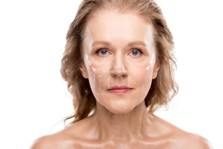 Photo for Mature woman with cosmetic cream on face looking at camera Isolated On White - Royalty Free Image