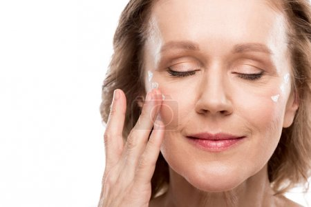 Foto de Mature woman applying cosmetic cream on face Isolated On White - Imagen libre de derechos