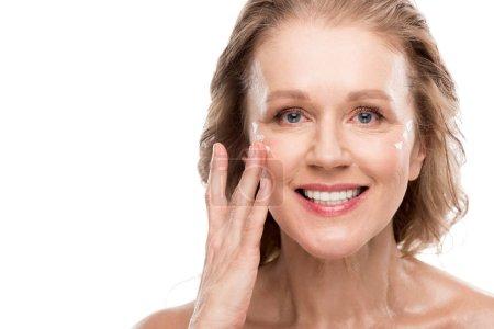 Photo pour Mature femme appliquant la crème cosmétique sur le visage isolé sur blanc - image libre de droit