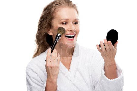 Photo pour Femme mûre dans le peignoir utilisant le miroir et la brosse de cosmétiques tout en appliquant le maquillage d'isolement sur le blanc - image libre de droit