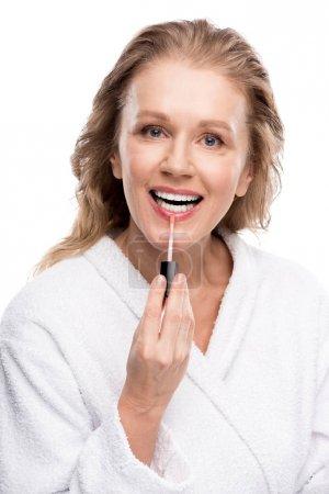 Photo pour Belle femme mûre de sourire appliquant le lustre à lèvres isolated on White - image libre de droit