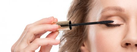 Photo for Panoramic shot of mature woman applying mascara Isolated On White - Royalty Free Image