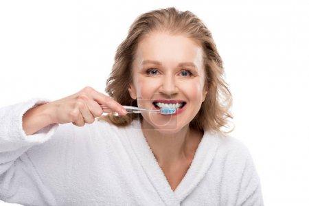 Photo pour Femme âgée moyenne brossant des dents d'isolement sur le blanc - image libre de droit