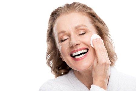 Photo pour Femme mûre de sourire essuyant le visage avec le tampon de coton d'isolement sur le blanc - image libre de droit