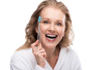 uśmiechnięta kobieta w średnim wieku w szlafrok z szczoteczką na białym tle