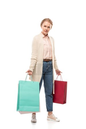 Photo for Middle aged woman with shopping bags looking at camera On White - Royalty Free Image