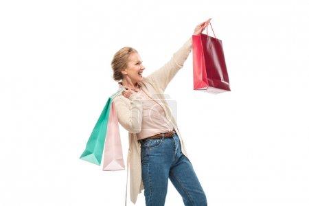 Photo pour Femme âgée moyenne excitée avec des sacs à provisions d'isolement sur le blanc - image libre de droit