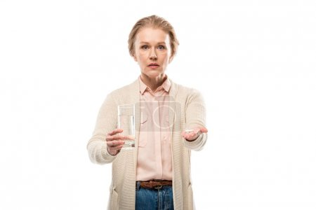 Photo pour Femme âgée moyenne avec le verre de l'eau et des pillules d'isolement sur le blanc - image libre de droit