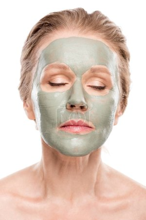Photo pour Mature woman with clay mask and eyes closed Isolated On White - image libre de droit