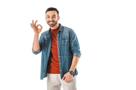 handsome cheerful man looking at camera and showing okay gesture isolated on white