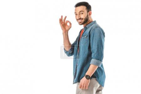 Photo pour Homme de sourire dans la chemise de denim affichant le geste correct et regardant l'appareil-photo d'isolement sur le blanc - image libre de droit