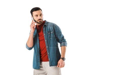Photo pour Homme barbu pensif dans la chemise de denim regardant en arrière tout en utilisant le smartphone isolé sur le blanc - image libre de droit