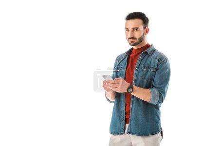 Photo pour Homme beau pensive dans la chemise de denim utilisant le smartphone d'isolement sur le blanc - image libre de droit