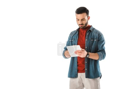 Photo for Thoughtful bearded man in denim shirt using digital tablet isolated on white - Royalty Free Image