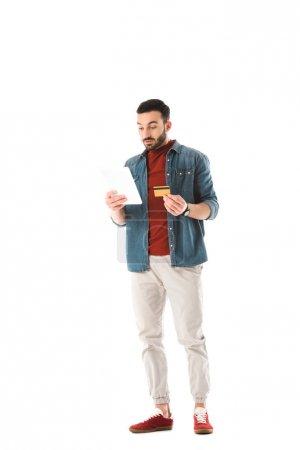 Photo pour Homme concentré retenant la carte de crédit tout en utilisant la tablette numérique isolée sur le blanc - image libre de droit