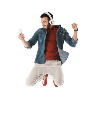 Photo for Excited man in headphones jumping while using smartphone and showing yes gesture isolated on white - Royalty Free Image