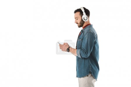 Photo pour Side view of handsome man in headphones using smartphone isolated on white - image libre de droit