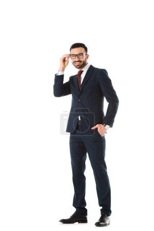 Photo pour Homme d'affaires de sourire restant avec la main dans la poche, touchant des glaces et regardant l'appareil-photo d'isolement sur le blanc - image libre de droit