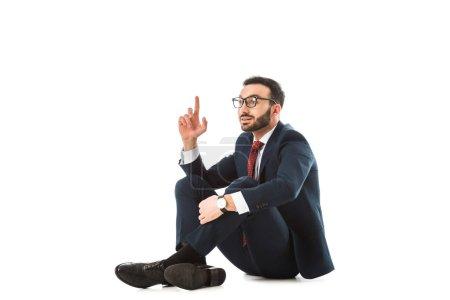 Photo pour Homme d'affaires de sourire affichant le signe d'idée tout en s'asseyant sur le fond blanc - image libre de droit