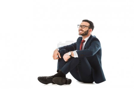 Photo for Smiling businessman in black suit looking away while sitting on white background - Royalty Free Image