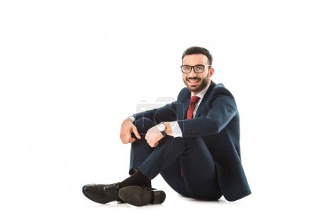 Photo for Happy businessman in glasses looking at camera while sitting on white background - Royalty Free Image