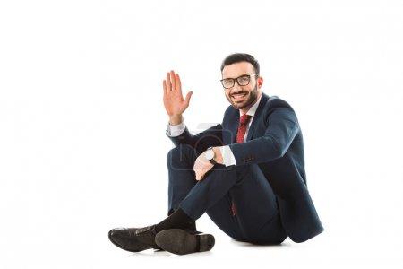 Photo pour Homme d'affaires joyeux montrant geste bonjour tout en étant assis sur fond blanc - image libre de droit