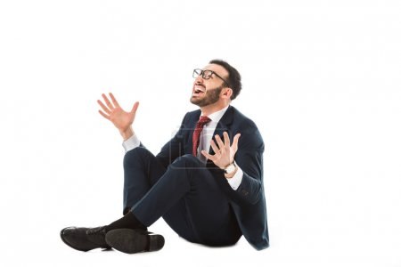 Photo for Happy businessman looking up and gesturing while sitting on white background - Royalty Free Image