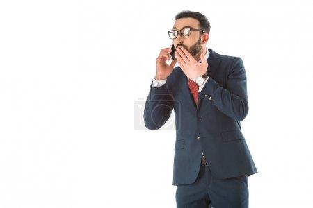 Photo pour Homme d'affaires choqué couvrant la bouche avec la main tout en parlant sur le smartphone isolé sur le blanc - image libre de droit