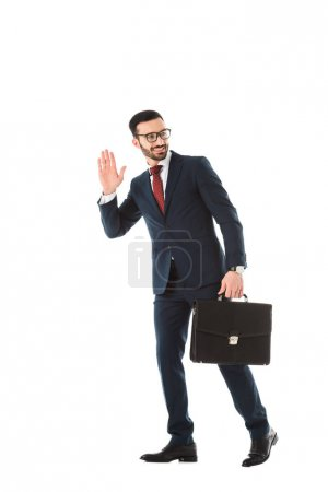 Photo for Smiling businessman with briefcase looking back and showing hello gesture isolated on white - Royalty Free Image