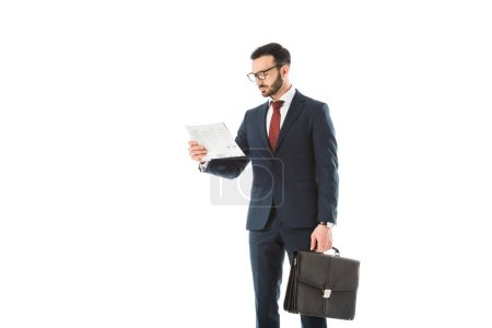 Photo for Concentrated businessman with briefcase reading newspaper isolated on white - Royalty Free Image