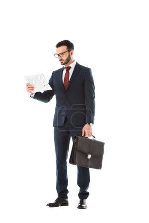 Photo for Attentive businessman with briefcase reading newspaper isolated on white - Royalty Free Image
