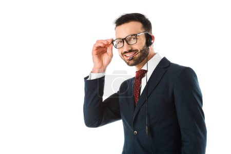 Foto de Smiling call center operator in headset looking at camera and touching glasses isolated on white - Imagen libre de derechos