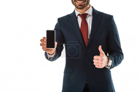 Foto de Cropped view of businessman showing thumb up while holding smartphone with blank screen isolated on white - Imagen libre de derechos