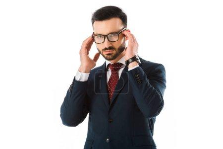 Photo pour Homme d'affaires beau dans les mains noires de fixation de procès près de la tête et regardant la caméra d'isolement sur le blanc - image libre de droit