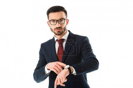 Photo pour Homme d'affaires confiant dans des glaces pointant à la montre et regardant l'appareil-photo isolé sur le blanc - image libre de droit