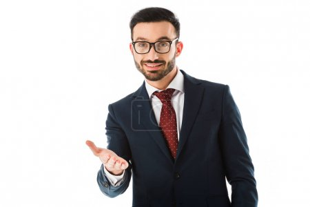 Foto de Smiling bearded businessman looking at camera with outstretched hand isolated on white - Imagen libre de derechos