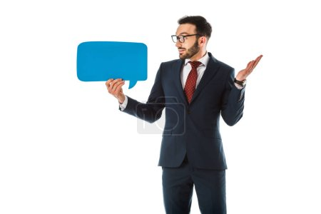 Photo for Discouraged businessman showing shrug gesture and looking at speech bubble isolated on white - Royalty Free Image