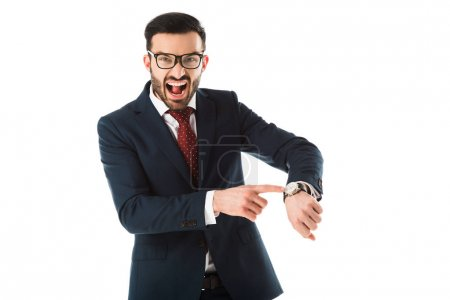 Foto de Angry businessman quarreling while looking at camera and pointing at watch isolated on white - Imagen libre de derechos