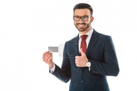 Photo pour Homme d'affaires gai retenant la carte de visite blanche et affichant le pouce vers le haut d'isolement sur le blanc - image libre de droit