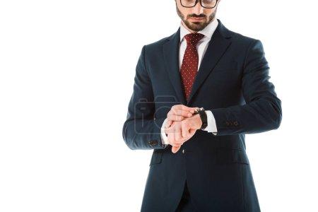 Photo pour Vue recadrée de l'homme d'affaires dans le procès noir regardant la montre d'isolement sur le blanc - image libre de droit