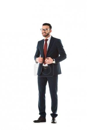feliz hombre de negocios en traje negro sonriendo y mirando hacia otro lado aislado en blanco