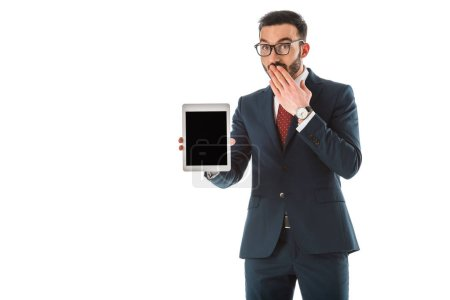 Photo for Surprised businessman holding digital tablet with blank screen and covering mouth with hand isolated on white - Royalty Free Image