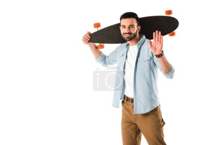 Photo for Cheerful man with longboard looking at camera and showing hello gesture isolated on white - Royalty Free Image