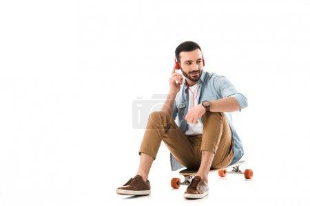 Photo pour Homme souriant assis sur longboard et parlant sur smartphone isolé sur blanc - image libre de droit