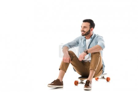 Photo for Happy man sitting on longboard and looking away isolated on white - Royalty Free Image