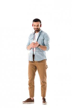 Photo pour Homme de sourire dans des écouteurs écoutant la musique et utilisant le smartphone d'isolement sur le blanc - image libre de droit